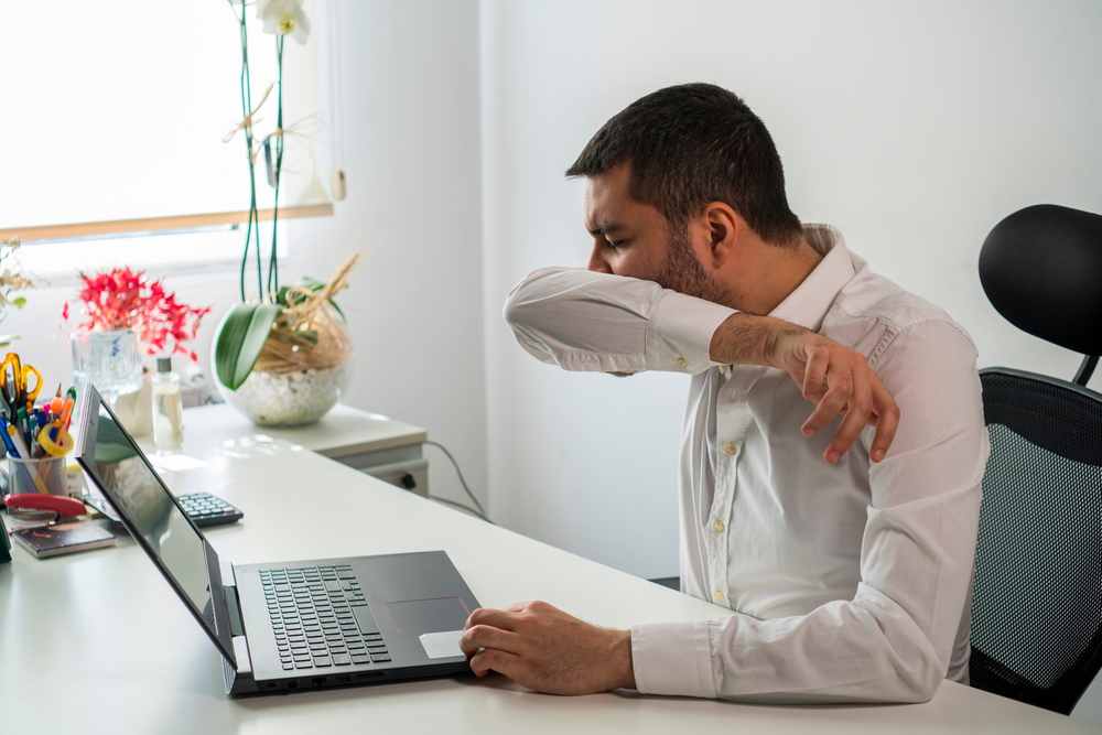 Man sneezing into his shirt sleeve while working on laptop