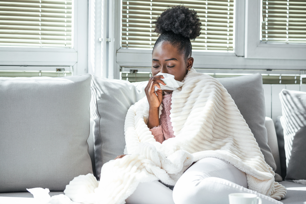 Woman sick with the flu sitting on the couch blowing her nose